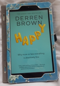 Kindle with the cover of Derren Brown's Happy on it. Cover is a sky blue background with the word Happy floating on it, the letters made out of golden mylar balloons.  Tagline for the book is, Why more or less everything is absolutely fine.